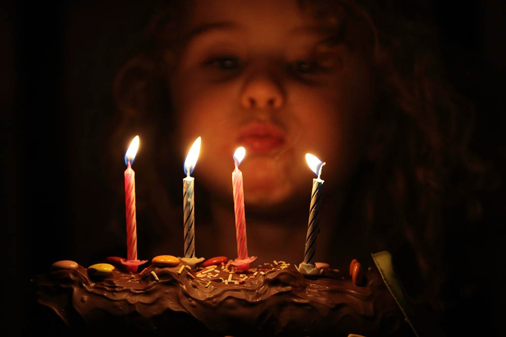 Party photography - blowing out candles on a birthday cake